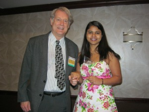 Jim Chamberlin and Arti Kumari pose with her trophy, clutching each others' hand