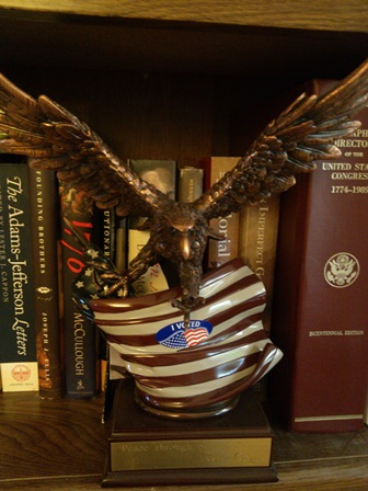 Eagle clutching American flag with an I Voted sticker on it, perched on a shelf of American history books