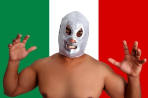 Wrestler in Mexican wrestling mask in front of Mexican flag