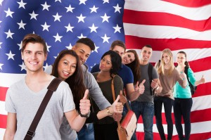 Line of diverse college students in front of an American flag background with thumbs up