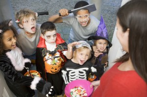 A diverse collection of kids in costume trick or treating