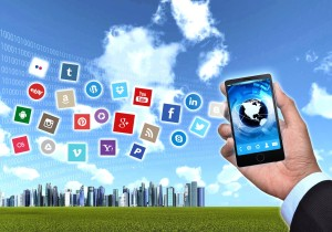 Photo of hand holding smart phone with social media icons flowing from it into a puffy clouded sky