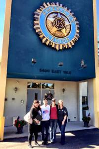 Foundation executives Summer Watson and Shelia Kirkbride pose outside American Legion Post 1 in Denver, Colorado, with two members of the post.