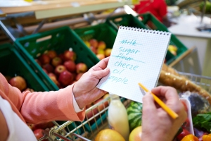 Woman's hands holding a shopping list of six items, two of which have been crossed out, over a shopping cart in the produce section