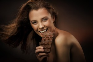 Cheerful woman eating chocolate © Can Stock Photo konradbak